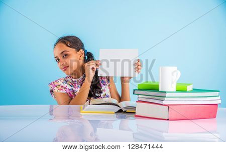 indian girl student holding white board while studying, indian girl studying and holding white card with copy space, asian girl holding white card and studying