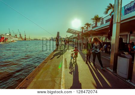 HAMBURG, GERMANY - JUNE 08, 2015: River pier on Hamburg, at the end of the day people can walk and go out with bycicles and childs.