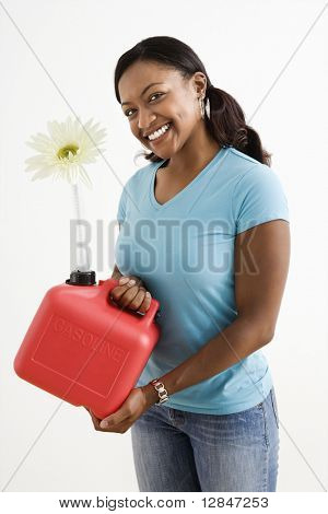 African American young adult female holding gas can with flower in it's nozzle.