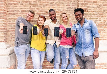 Multiracial group of friends showing blank smartphone screens outdoors - Young multi ethnic people having fun with mobile phones - Technology addiction concept - Soft focus on faces