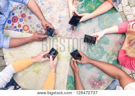 Multiracial group of friends mobile addicted - Wifi connected people in bar table meeting - Top view hands circle using mobile phones - New trends and teamwork concept - Soft focus on bottom hands -
