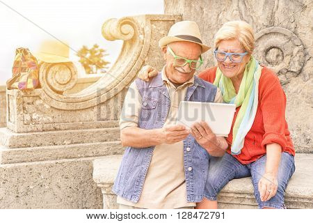 Senior couple surfing online with digital tablet in old european town center - Concept of active elderly and interaction with new technologies - Interaction with new trends and technologies