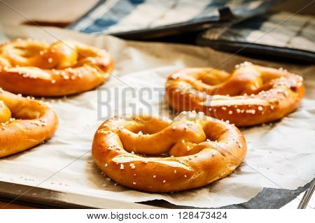 Fresh baked pretzels on a baking sheet.