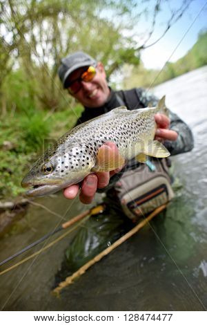 Happy fly-fisherman holding fario trout
