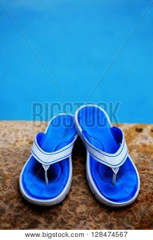 Detail of blue flip flops for summer next to swimming pool