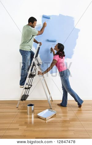 African American male and female couple painting wall blue and smiling at each other.