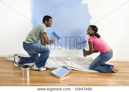 African American male and female couple painting wall blue.