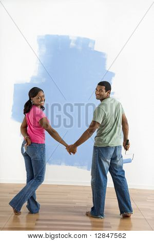 African American couple standing together in front of half-painted wall looking at viewer.