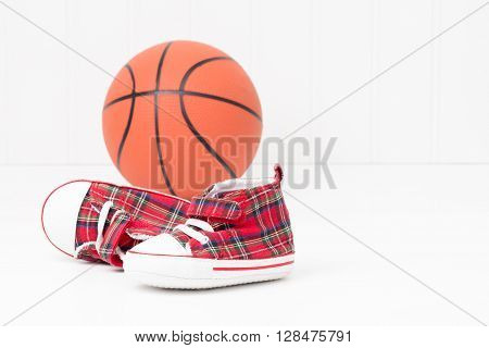 Pair of baby sized athletic shoes in front of a basketball.