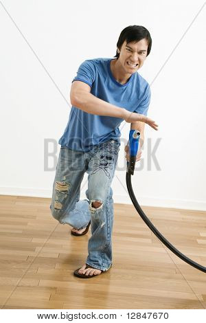 Asian young man aiming gasoline pump nozzle like a gun.