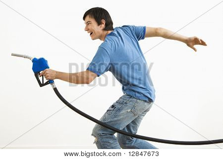 Asian young man aiming gasoline pump nozzle like a gun.