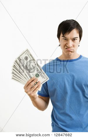 Asian young man holding money with disgust on his face.