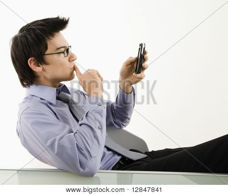Asian businessman sitting at desk texting using his smart phone.