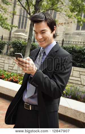 Asian business man standing looking at cell phone messages smiling.