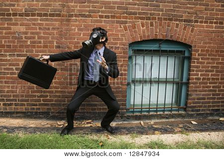 Businessman standing next to brick wall wearing gas mask in fighting stance.
