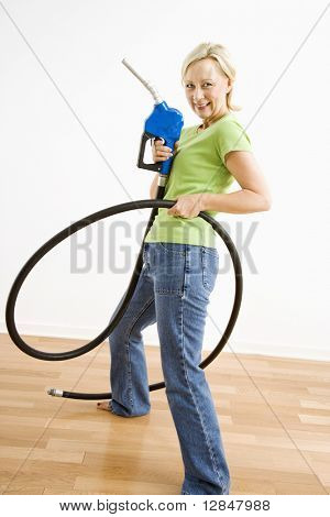 Portrait of adult blonde woman holding gas nozzle like a gunslinger.