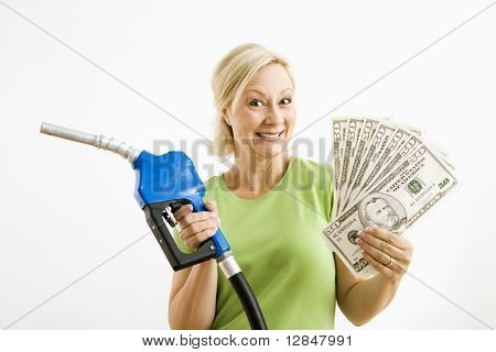 Portrait of smiling adult blonde woman holding gas nozzle and lots of money.