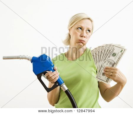 Portrait of distressed adult blonde woman holding gas nozzle and lots of money.