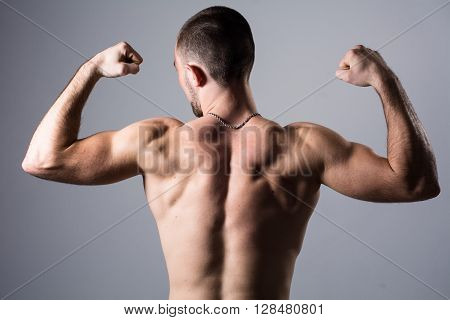 Portrait of a handsome muscular young man from the back. Shot in a studio.