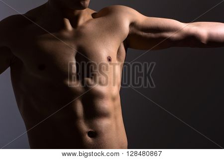 Close up of a sports man's chest. Muscular man on a dark background