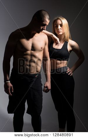 Man with a naked torso and a girl. Athletes on a dark background in the studio
