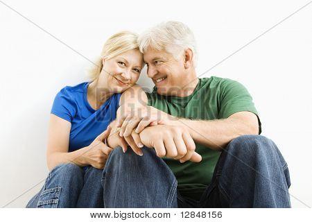 Casal de meia-idade sentado juntos sorrindo.
