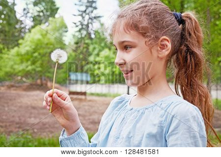 Humeral outdoor portrait of smiling girl with blowball in her hand.