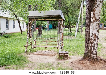 Swings on chains made of birch branches and trunks.