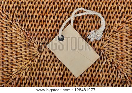 Empty paper tag on wickered wooden background
