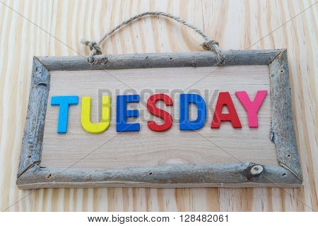 Tuesday word with colorful letter on Wood Background