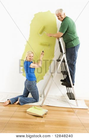 Middle-aged couple painting wall green and looking at viewer.