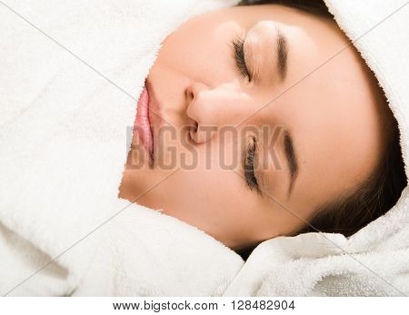 Closeup headshot young woman lying down comfortably, eyes closed with head covered in white towels.