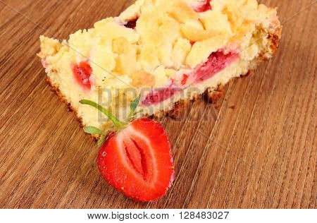 Fresh baked yeast cake with crumble and strawberries on wooden surface concept for dessert