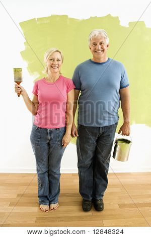 "Portrait of happy adult couple standing in front of half-painted wall with paint supplies ""American Gothic"" style."