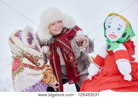 Mother and little daughter near stuffed Maslenitsa in winter park.