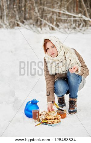 Teenage girl opens glass jar with honey near blue jug, glass cup with beverage, plate with pancakes on snow.