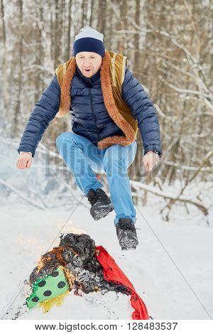 Man jumps over burning Maslenitsa in winter park.