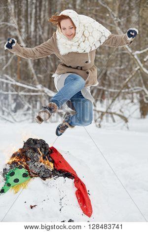 Teenage girl jumps over burning stuffed Maslenitsa in winter park.