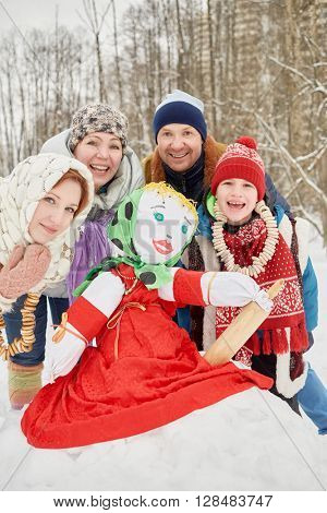 Happy family of four around stuffed dummy Maslenitsa in winter park.