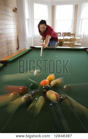 Man shooting game of pool with balls scattering after hit.