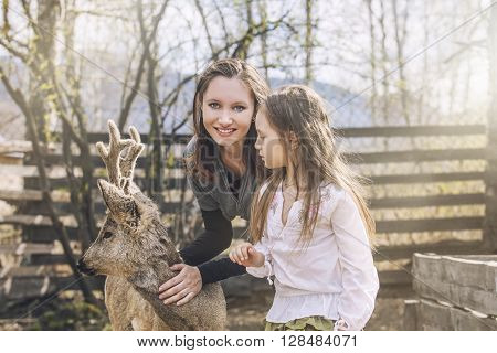 Beautiful little girl and her mom hugging animal ROE deer in the sunshine protecting an animal