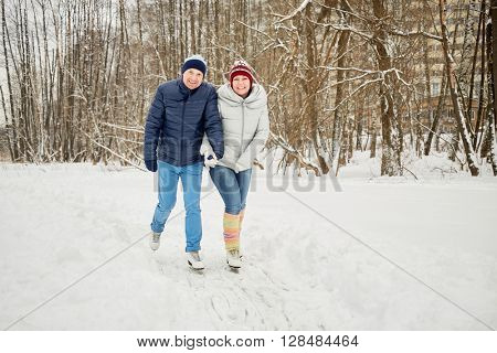 Smiling woman and man skate at ice pathway in winter park.