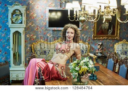 Woman dressed in oriental costume poses sitting on table in old-fashion style room.