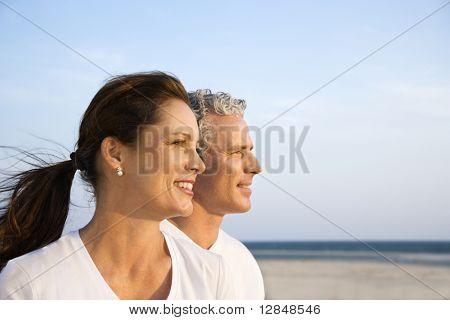 Vista lateral de sorrindo meio envelhecido casal na praia olhando fora na distância juntos. Horizontal