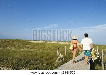 Man and woman wearing swimwear hold hands and walk down a boardwalk. Horizontal shot.