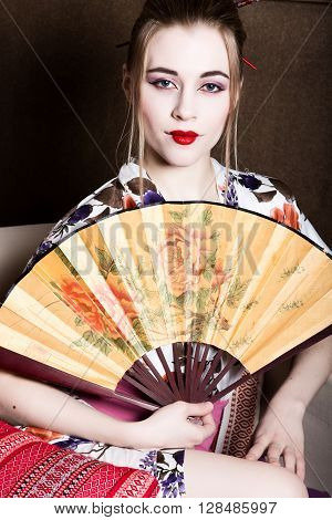 beautiful girl dressed as a geisha, she holds a chinese fan. Geisha makeup and hair dressed in a kimono. The concept of traditional Japanese values.