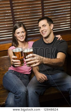 Young man and woman sitting together toasting their beers at pub looking at viewer. Vertical shot.
