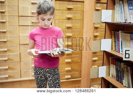Teenage girl stands reading book near bookshelves in library.