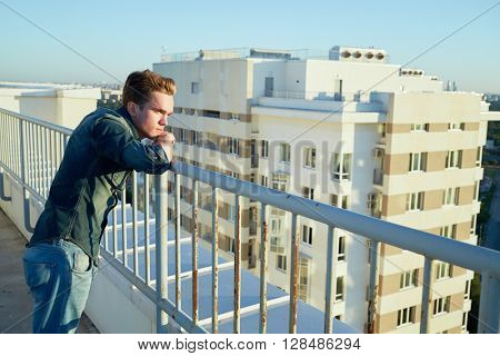 Young man in denim clothes stands on the building roof leaning to the fencing.