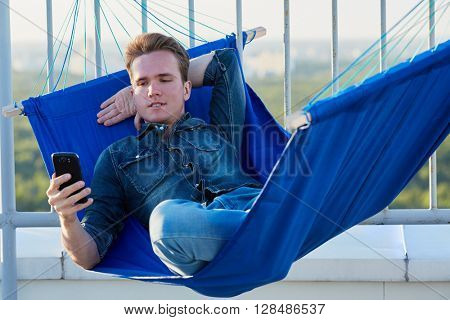 Young man in denim clothes lies in hammmock attached to roof fencing and looks at phone in his hand.
